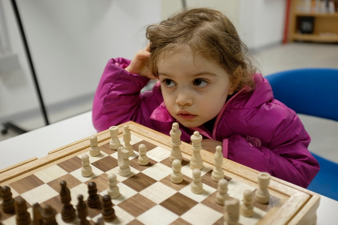 Child playing wooden chess