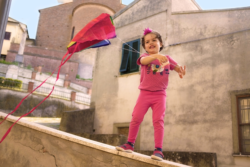 Child Standing on a wall flying a kite