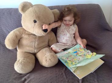 toddler reading book to teddy bear